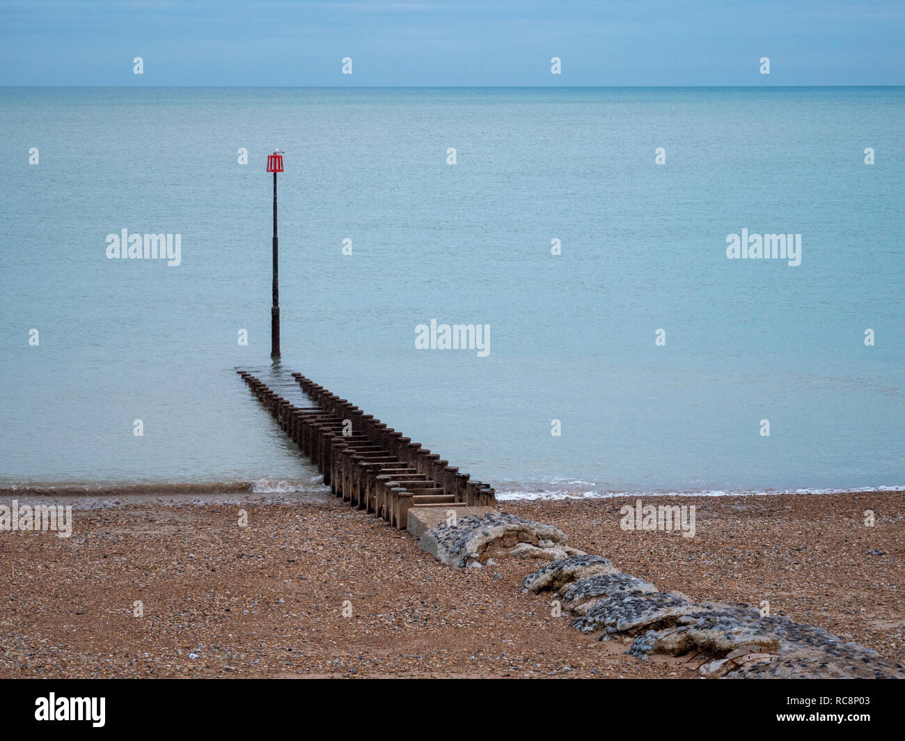A view of a red marker post and groynes at the sshingle beach at Eastbourne UK on an overcast winter day with muted colours. - Stock Image