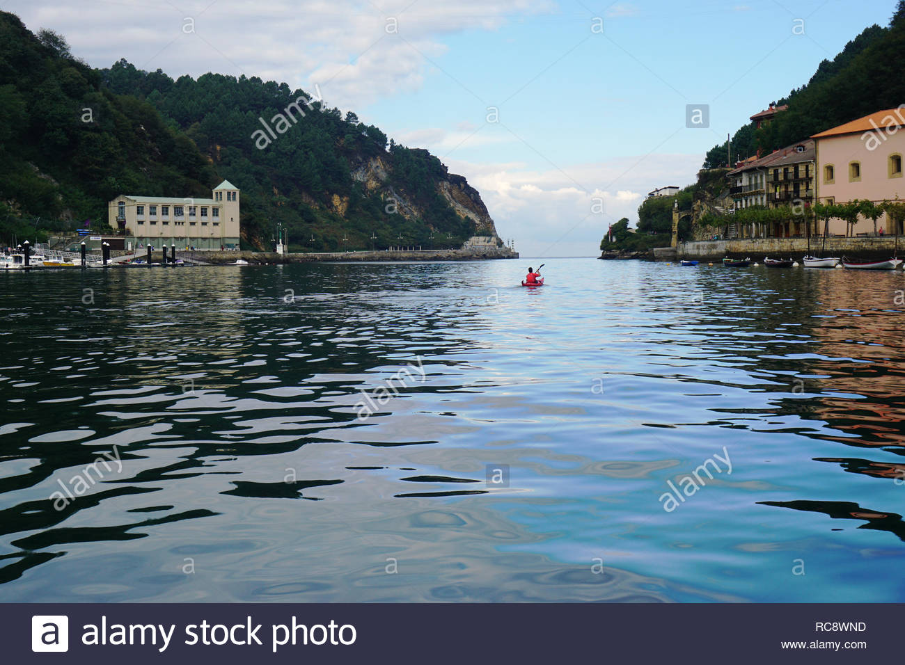 Red conoe on the river of the bay of pasaia in basque country in northern spain - Stock Image