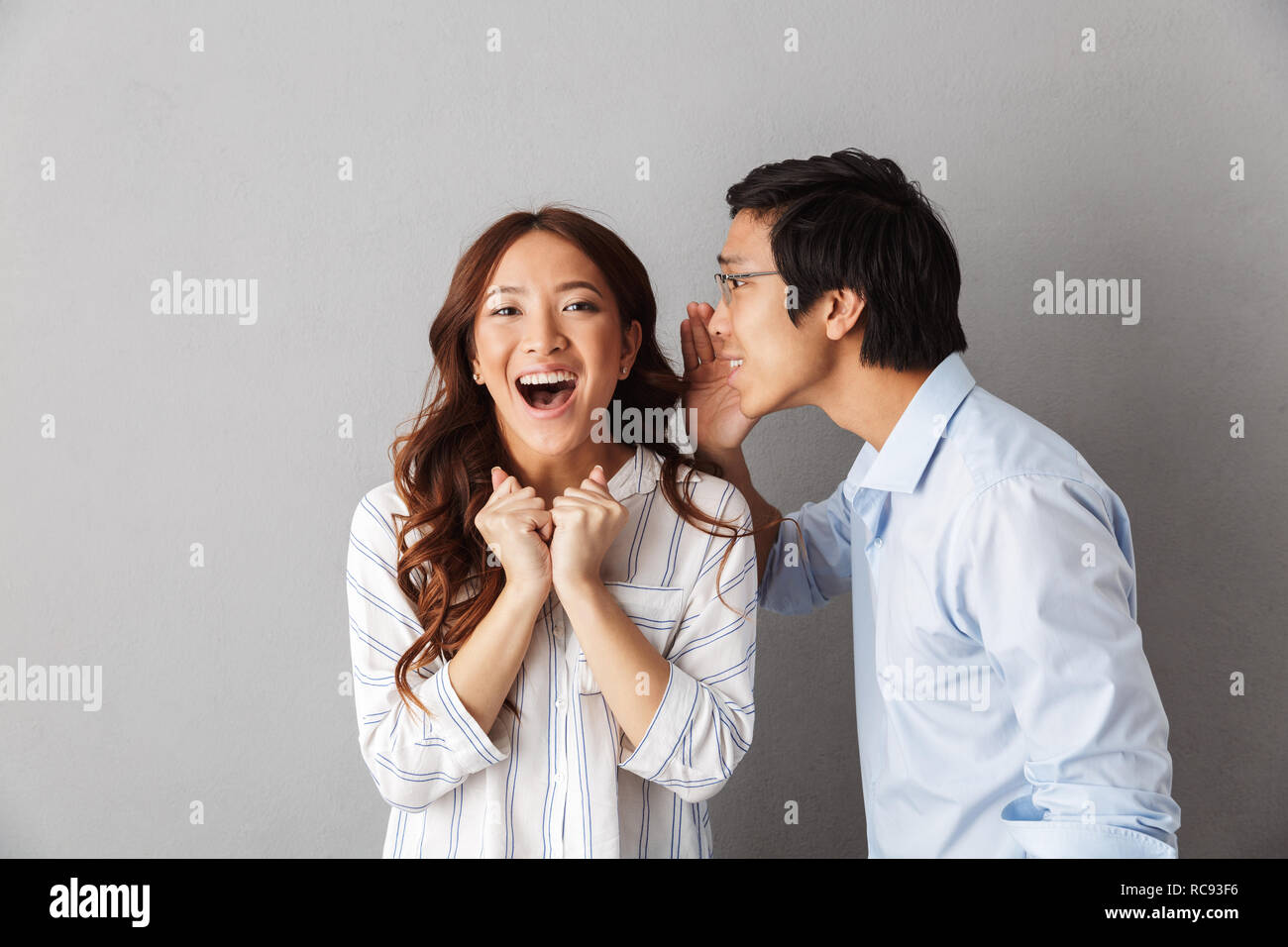 Excited asian couple standing isolated over gray background, telling secrets to each other - Stock Image