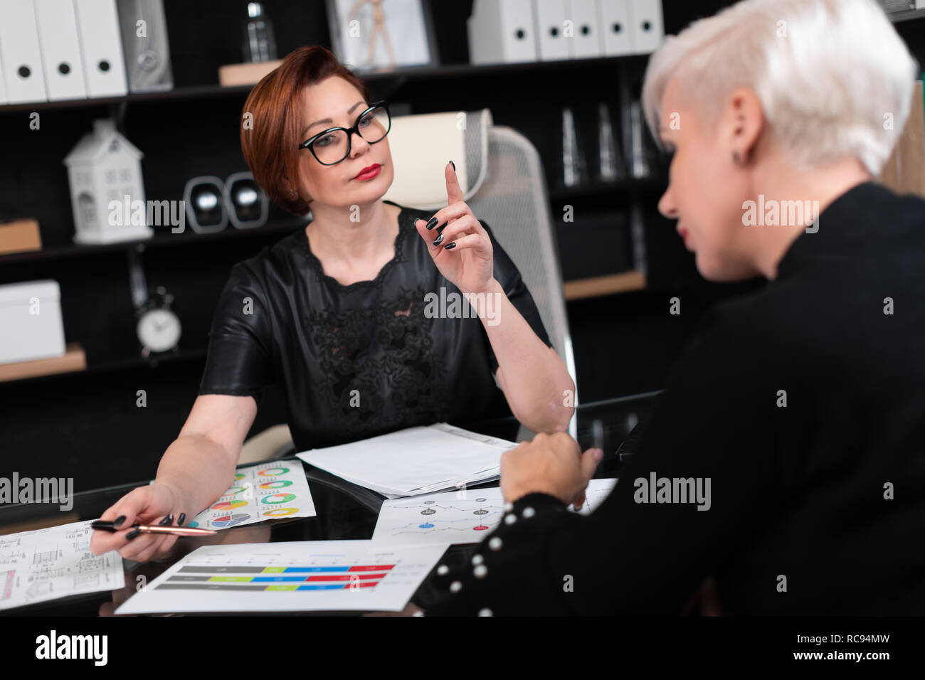 Business women discuss diagrams at Desk in office - Stock Image