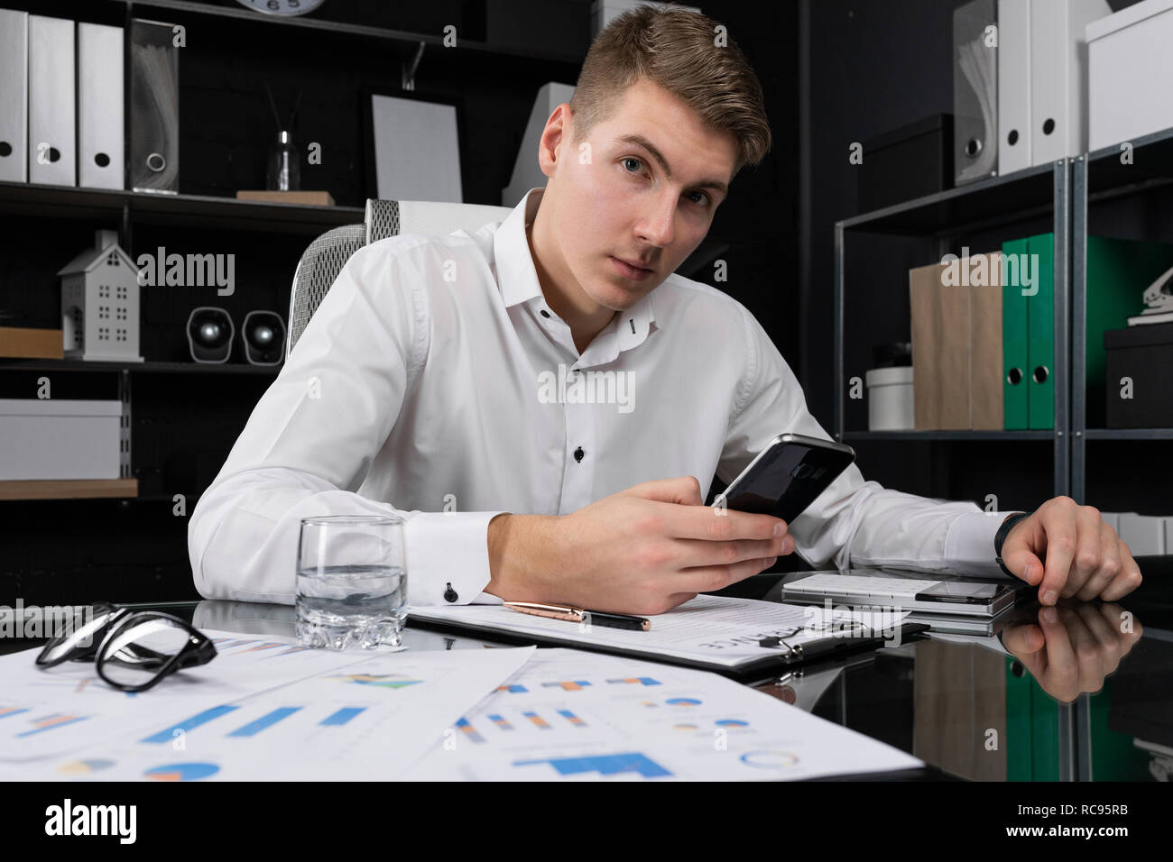young man with mobile phone in his hands sitting at table in bright office Stock Photo