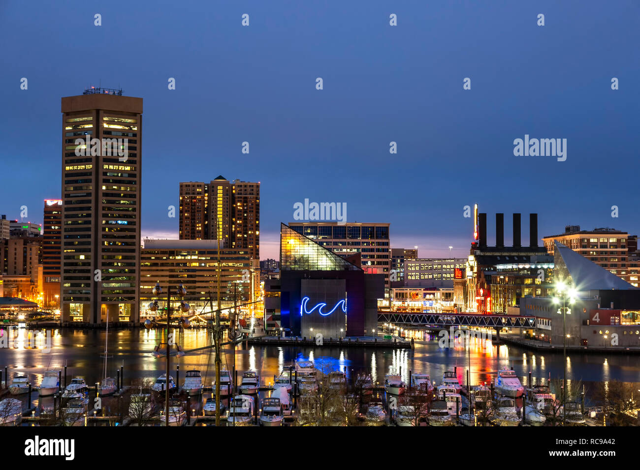 Baltimore Skyline at twilight, National Aquarium (with neon wave), and boats in marina, Inner Harbor, Patapsco River, Baltimore, Maryland USA - Stock Image