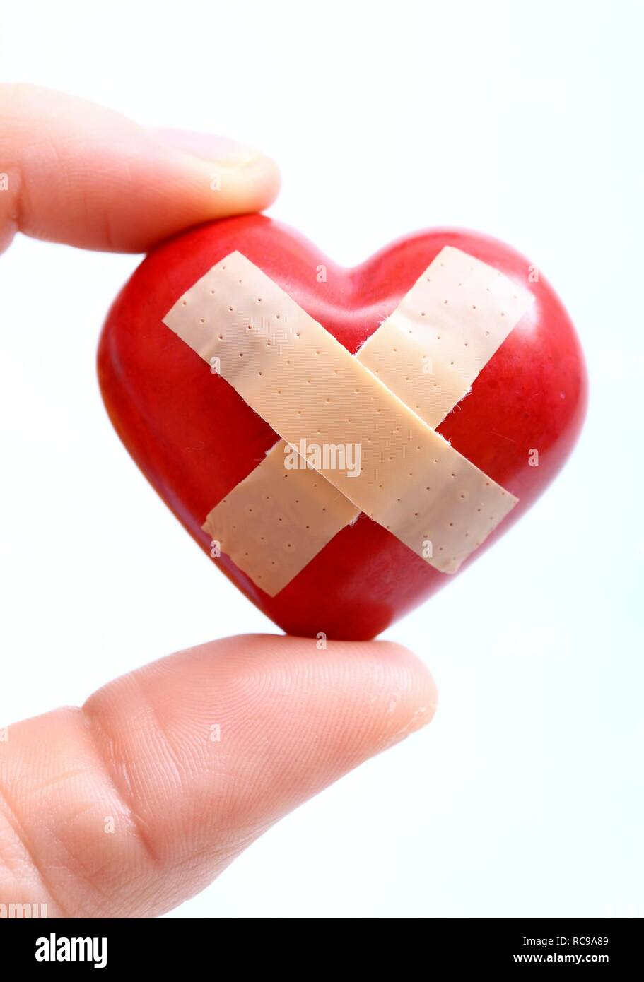 Hand holding a red heart with a plaster, symbolic image for heart disease, heart attack, a diseased heart - Stock Image