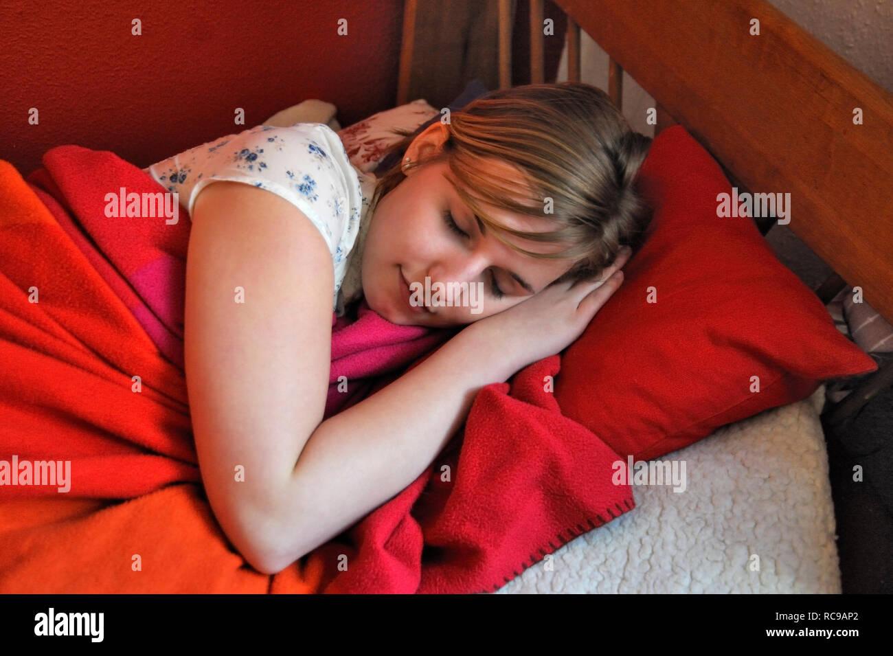 jugendliches Mädchen schläft in ihrem Zimmer | young female teenager sleeping in her bed - Stock Image