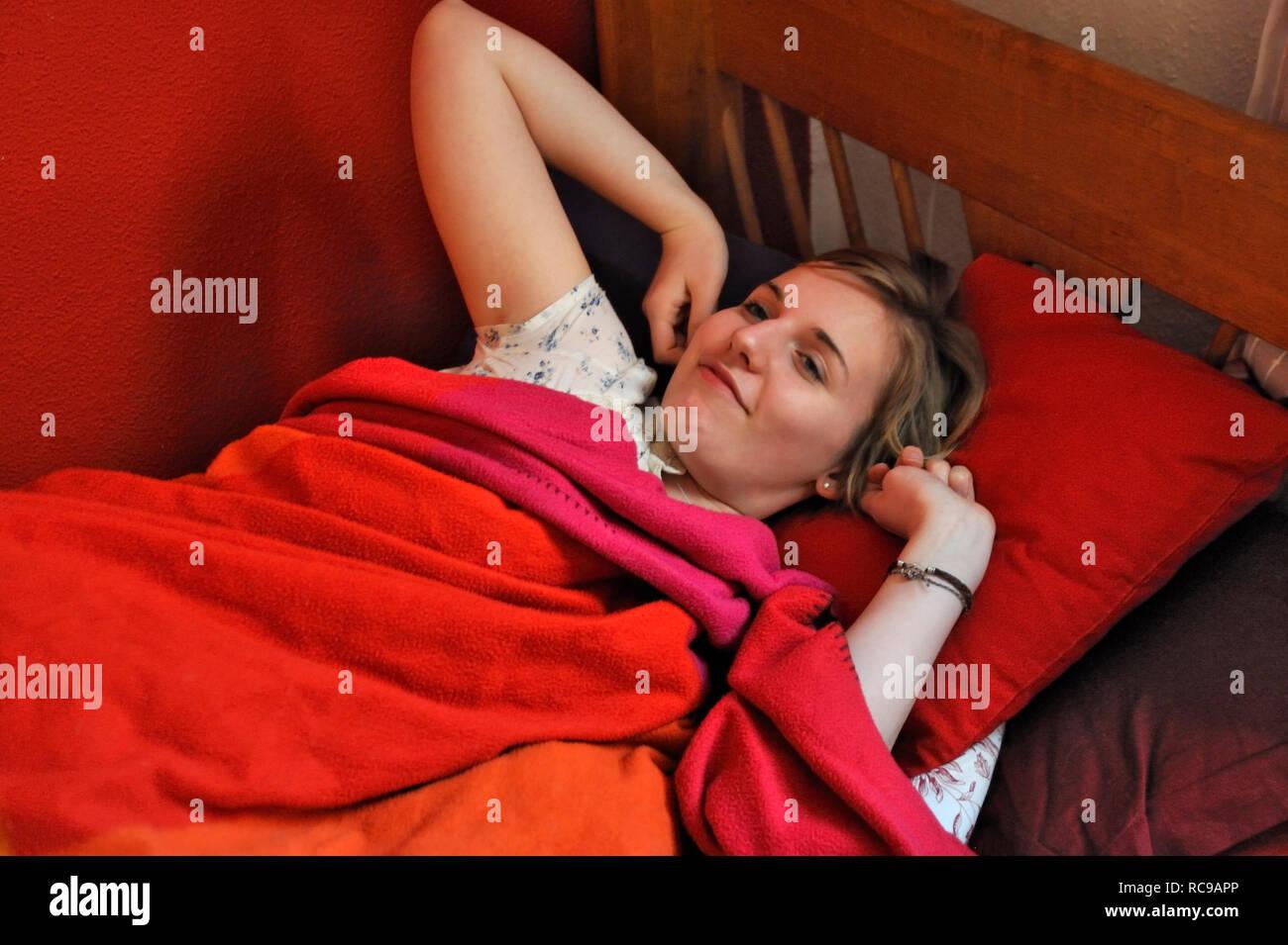 jugendliches Mädchen beim Aufwachen | young female teenager waking up - Stock Image