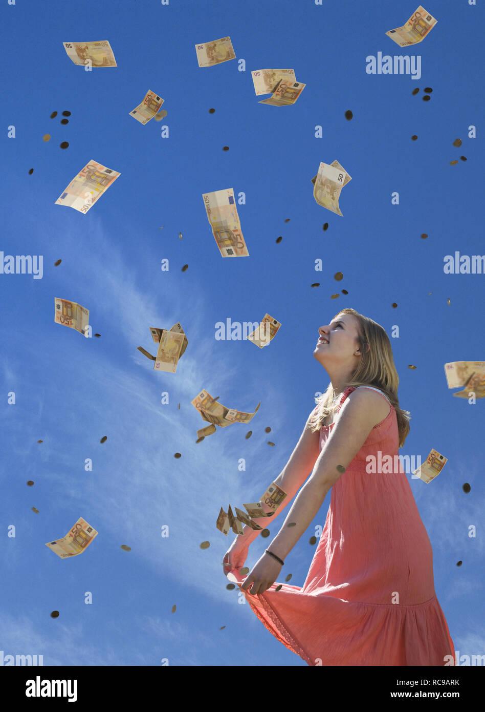 jugendliches Mädchen empfängt Geldregen | young female teenager receiving money rain - Stock Image