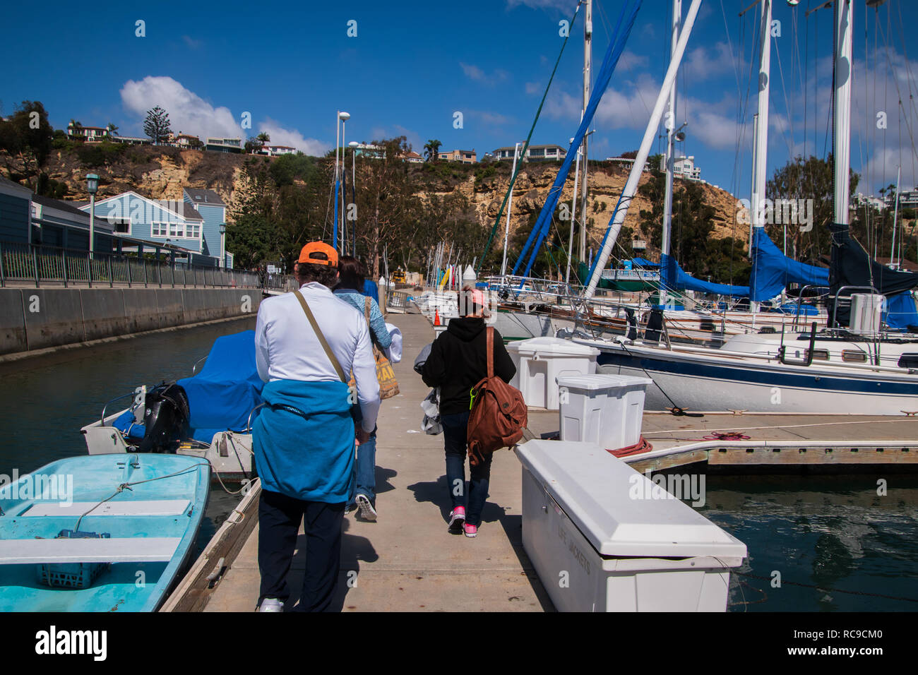 Three adult caucasians, on man and two women, walking away with only their backs visible. Walking on bock past sailboats and small motorboats - Stock Photo