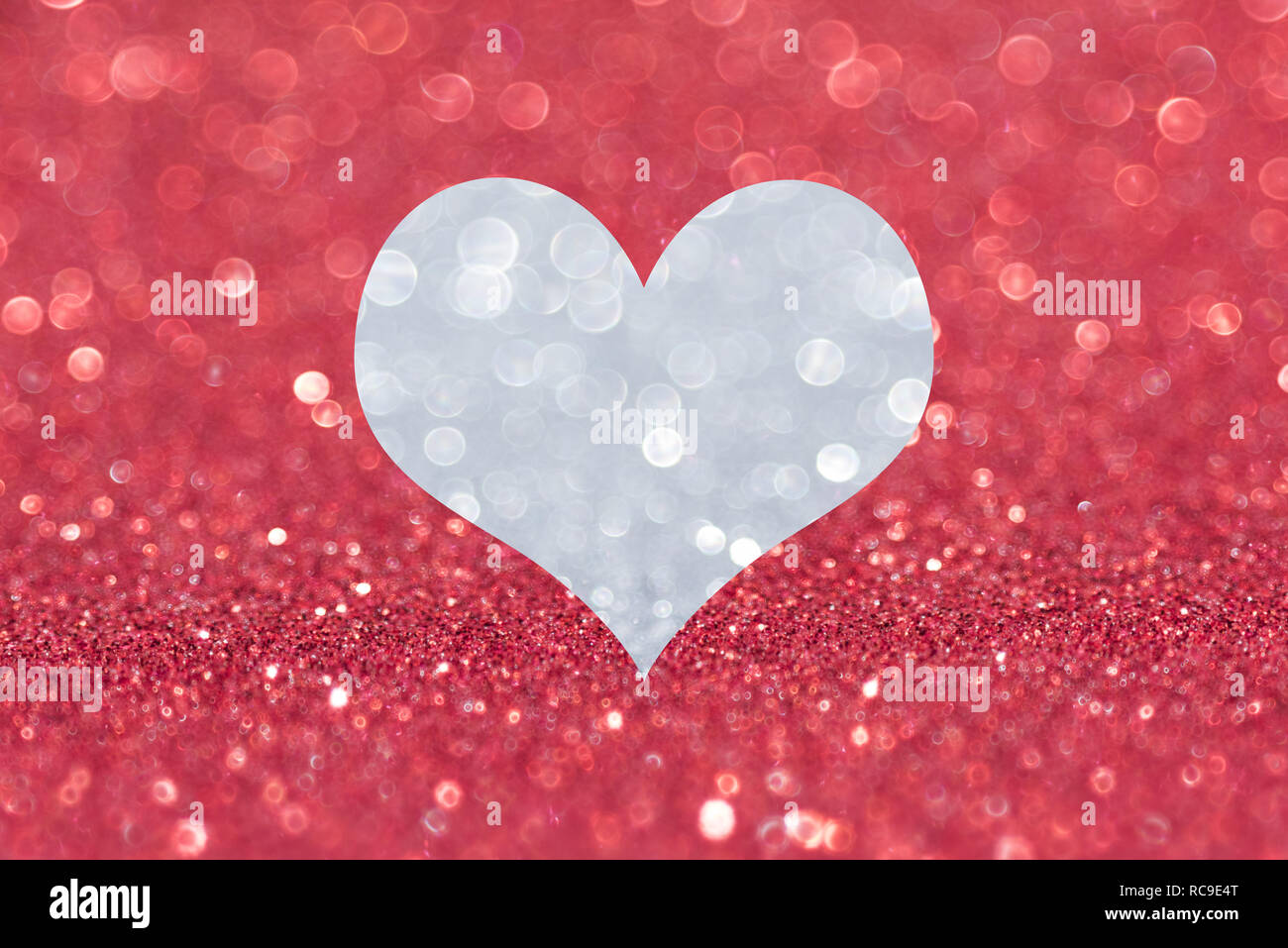Shiny red background with silver heart - Stock Image