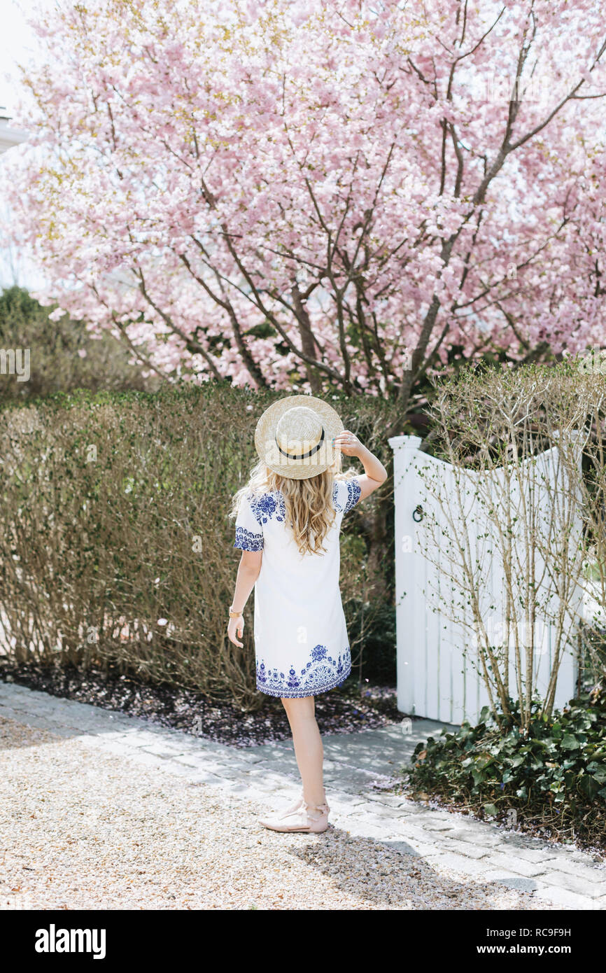 Young woman in straw boater in front of pink tree blossom, rear view, Menemsha, Martha's Vineyard, Massachusetts, USA - Stock Image