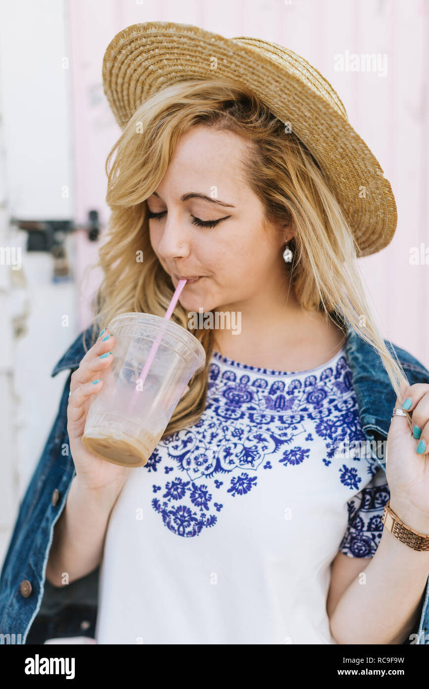 Young woman wearing boater drinking iced coffee from straw, Menemsha, Martha's Vineyard, Massachusetts, USA - Stock Image