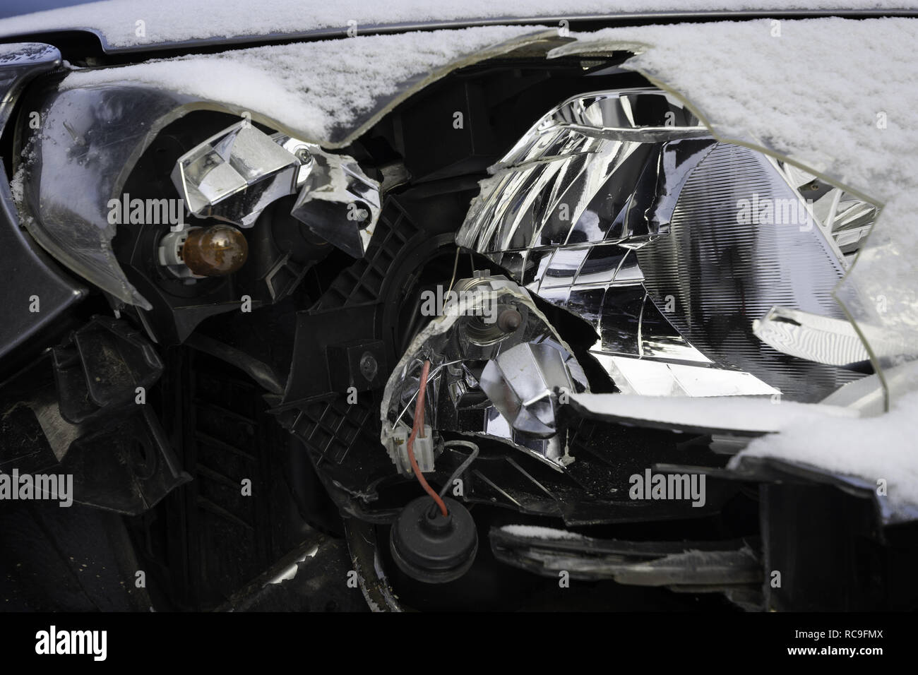 Broken car light accident. Close up of damaged headlight in a front of car, winter. - Stock Image
