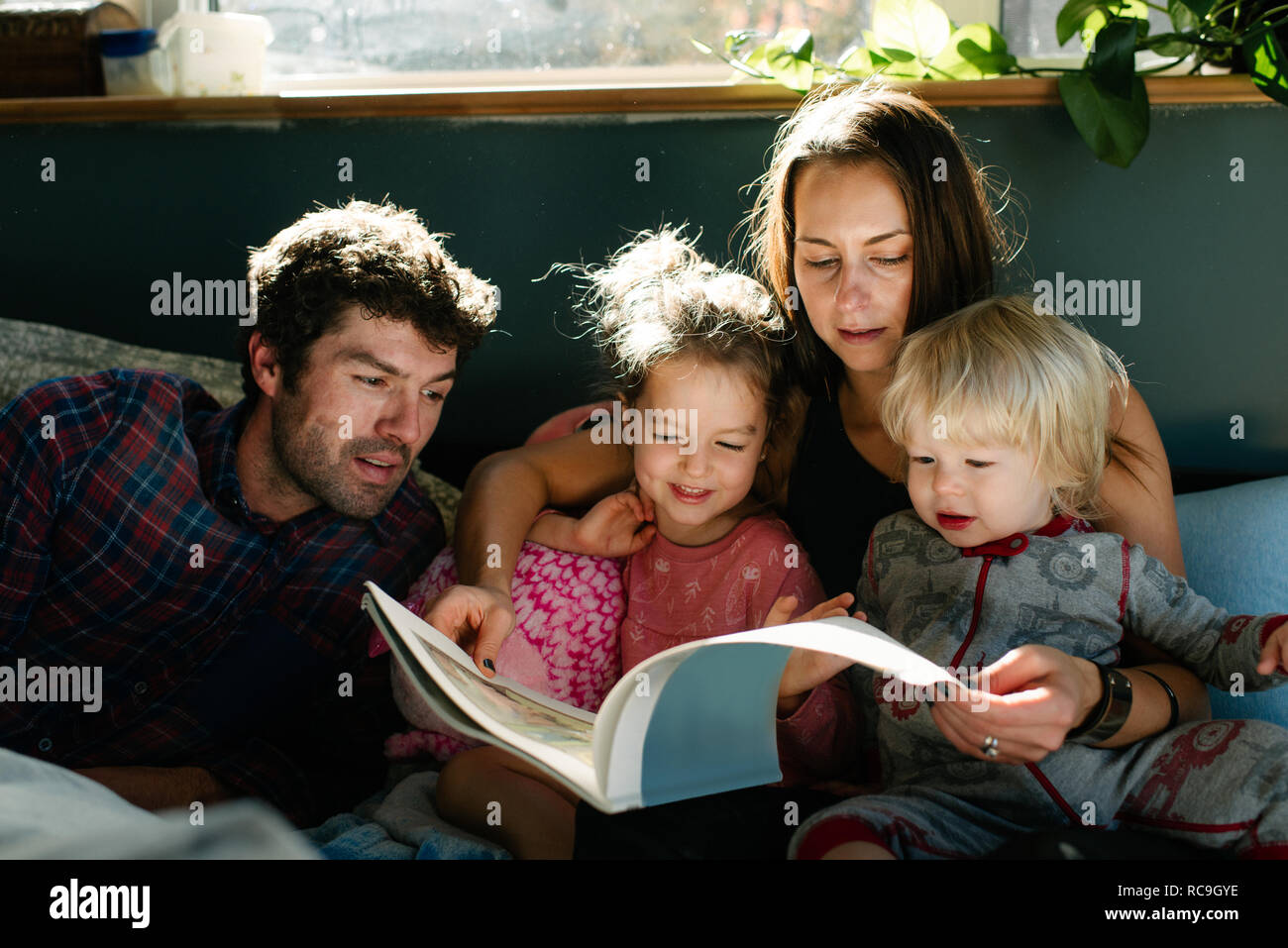 Parents reading to children in bed Stock Photo