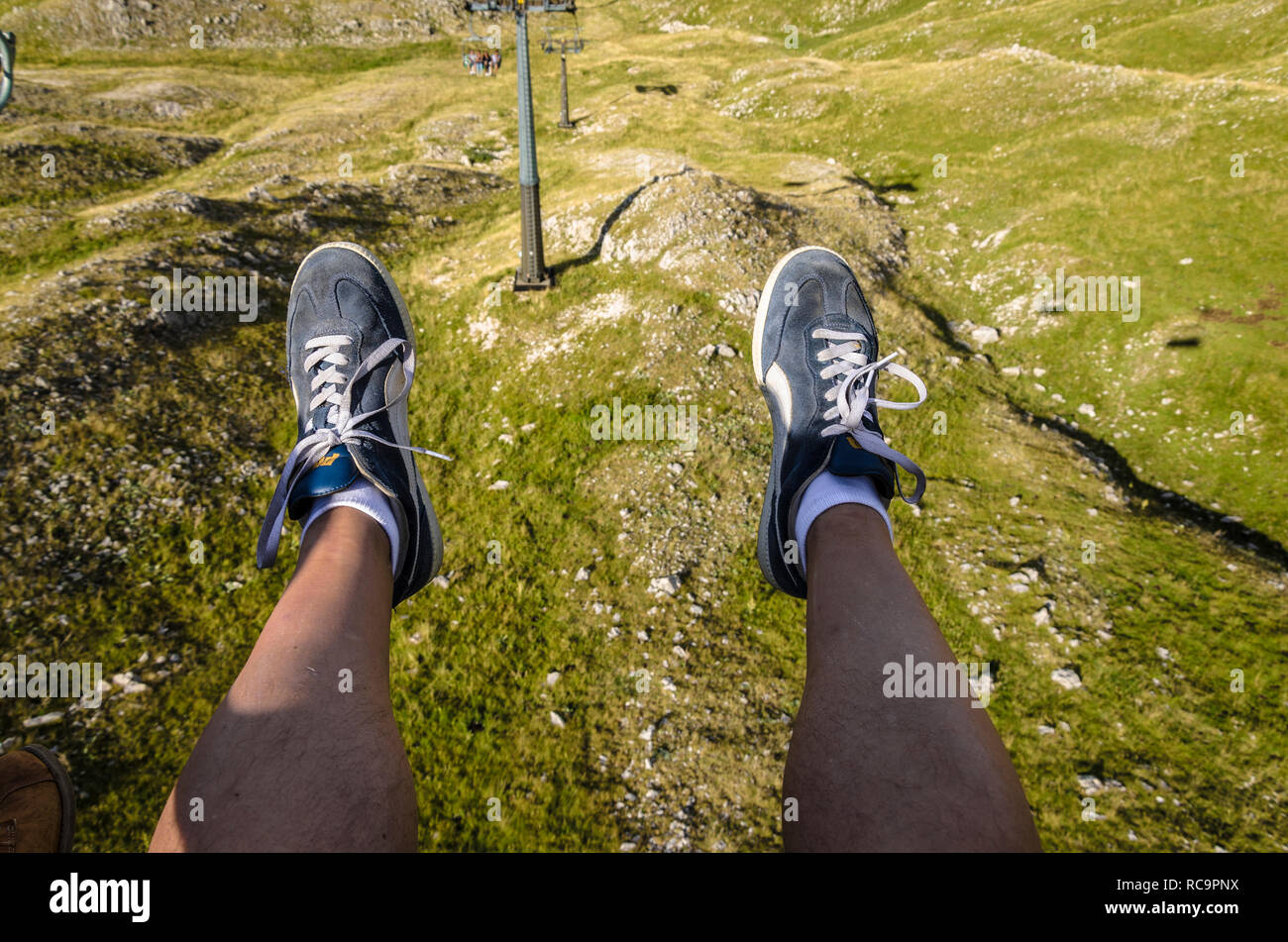 Panoramic view of a tourist on the chairlift downhill from the mountain - Stock Image