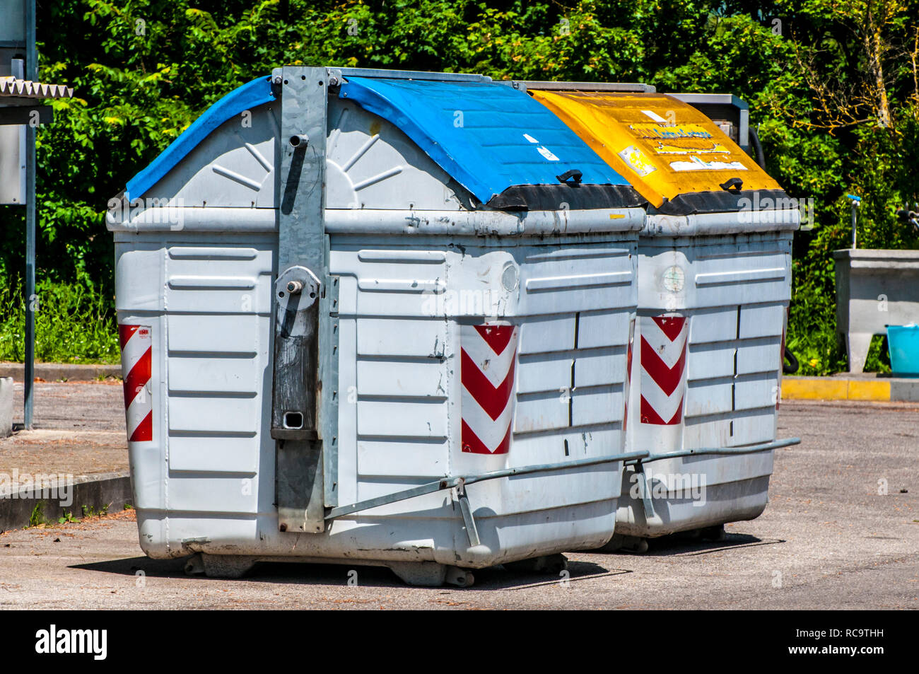 Containers for recycling in an urban street with labels for paper and cardboard and undifferentiated - Stock Image