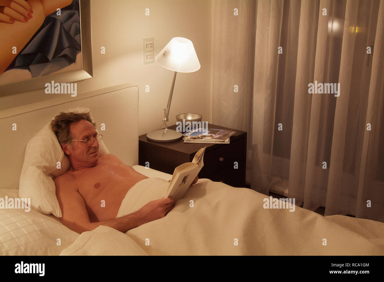 Mann mittleren Alters liest ein Buch im Bett | middleaged man is reading a book in bed - Stock Image