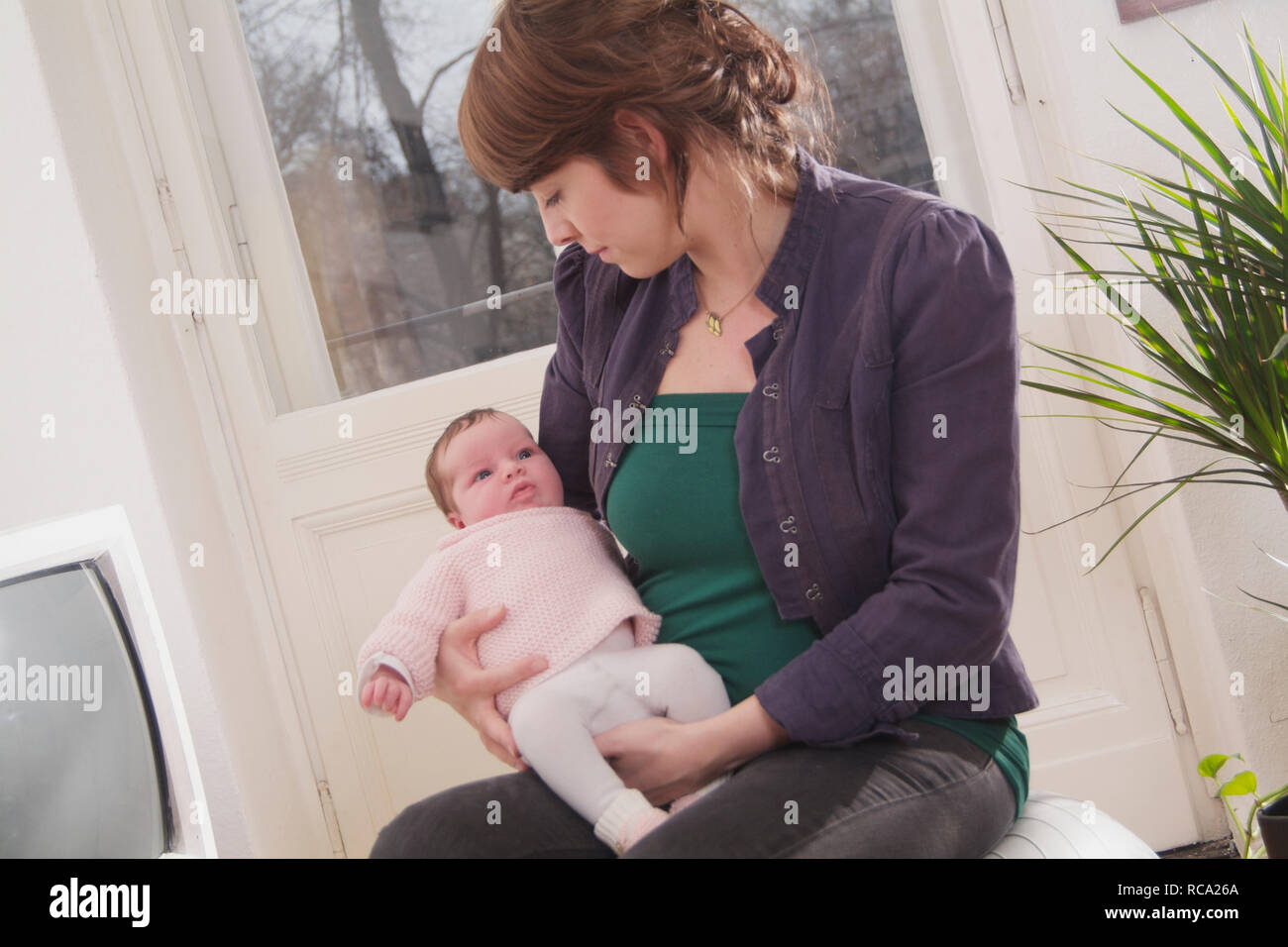 Junge Mutter hält ihre neugeborene Tochter im Arm, das Kind ist 12 Tage alt | young mother holding her new born baby in her arms - the baby ist 12 day Stock Photo