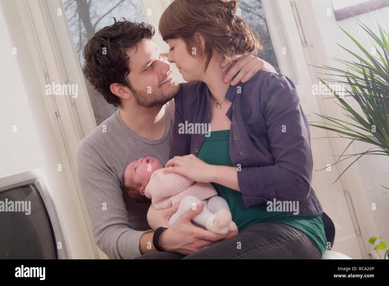 Junge Eltern halten ihre neugeborene Tochter im Arm, das Kind ist 12 Tage alt | young parents holding her new born baby in her arms - the baby ist 12  Stock Photo