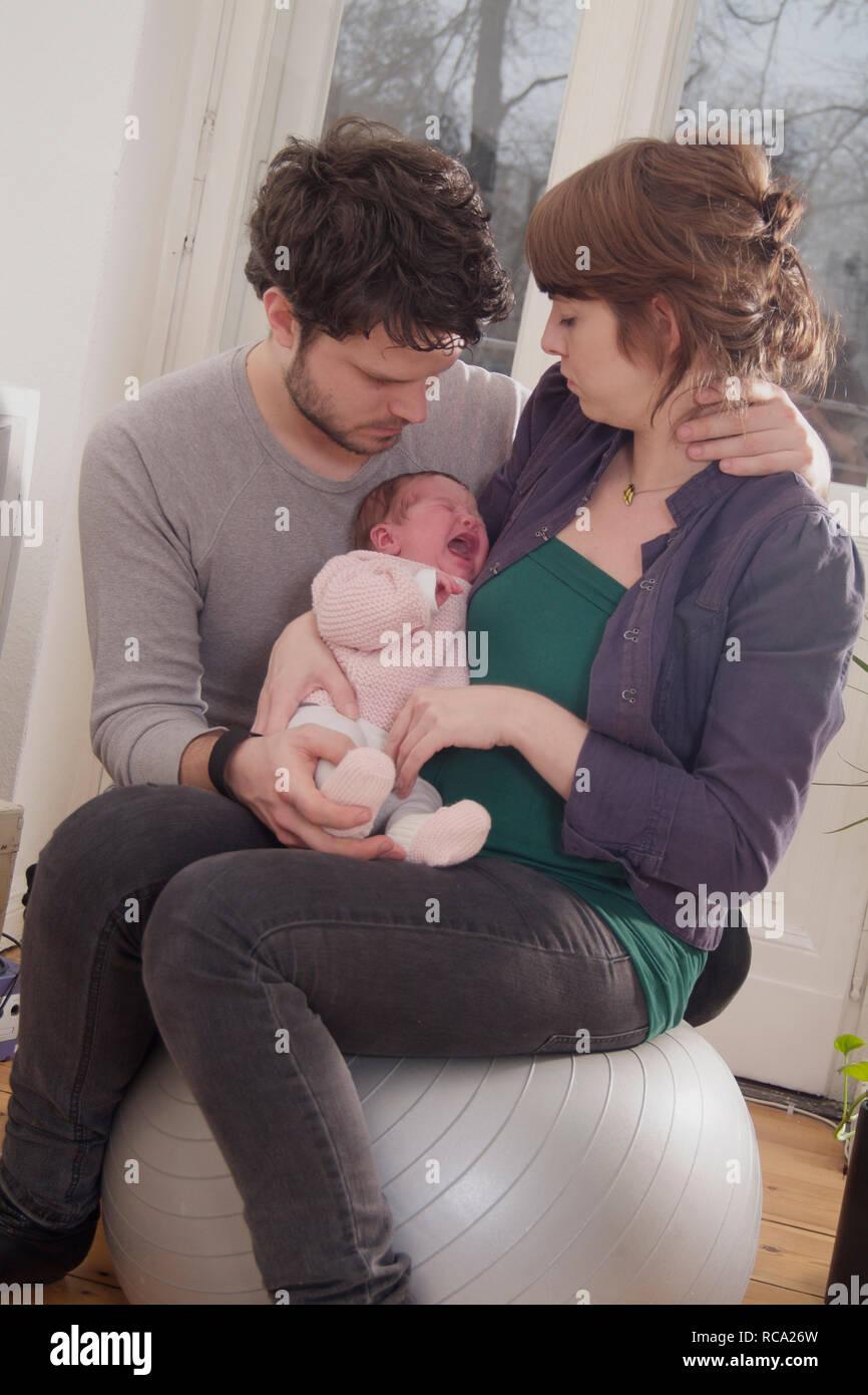 Junge Eltern halten ihre neugeborene Tochter im Arm, das Kind ist 12 Tage alt und schreit | young parents holding her new born baby in her arms - the  Stock Photo