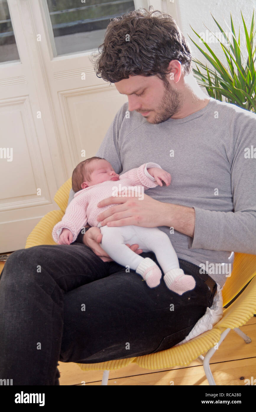Junger hält seine neugeborene Tochter im Arm, das Kind ist 12 Tage alt | young father holding his new born baby in his arms - the baby ist 12 days old Stock Photo