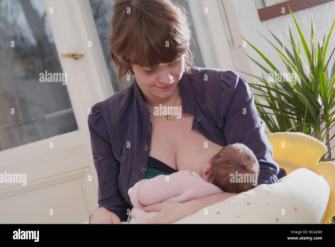 Junge Mutter stillt ihre neugeborene Tochter, das Kind ist 12 Tage alt   young mother nursing her new born baby - the baby ist 12 days old. child, chi Stock Photo