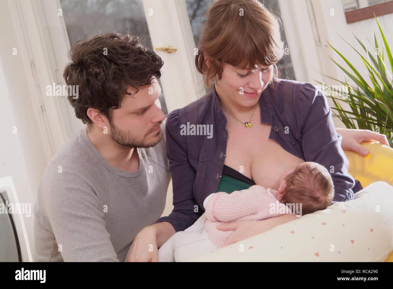 Junge Eltern beim Stillen ihrer neugeborenen Tochter, das Kind ist 12 Tage alt | young parents nursing their new born baby - the baby ist 12 days old. Stock Photo