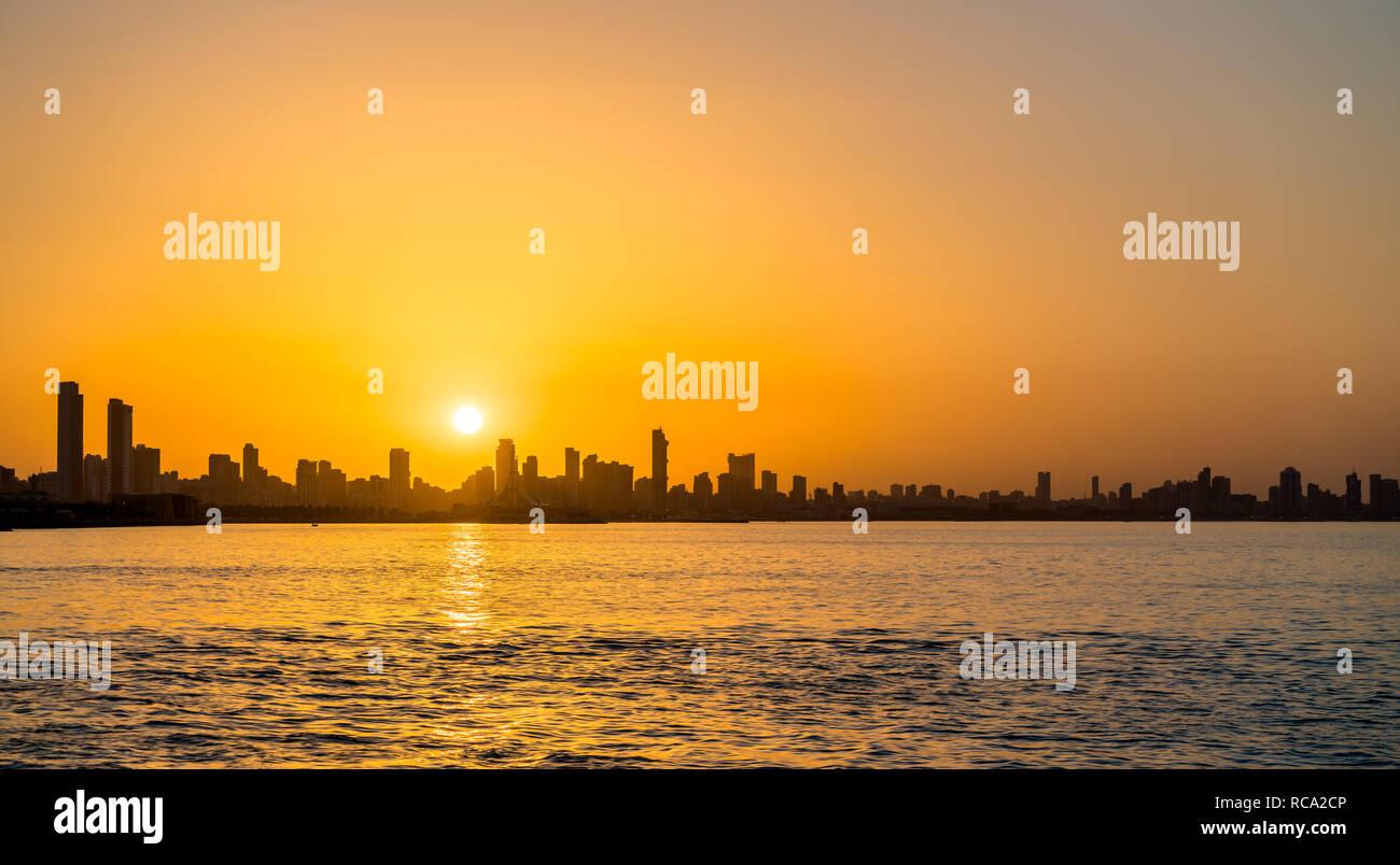 Skyline of Kuwait City at sunset. - Stock Image