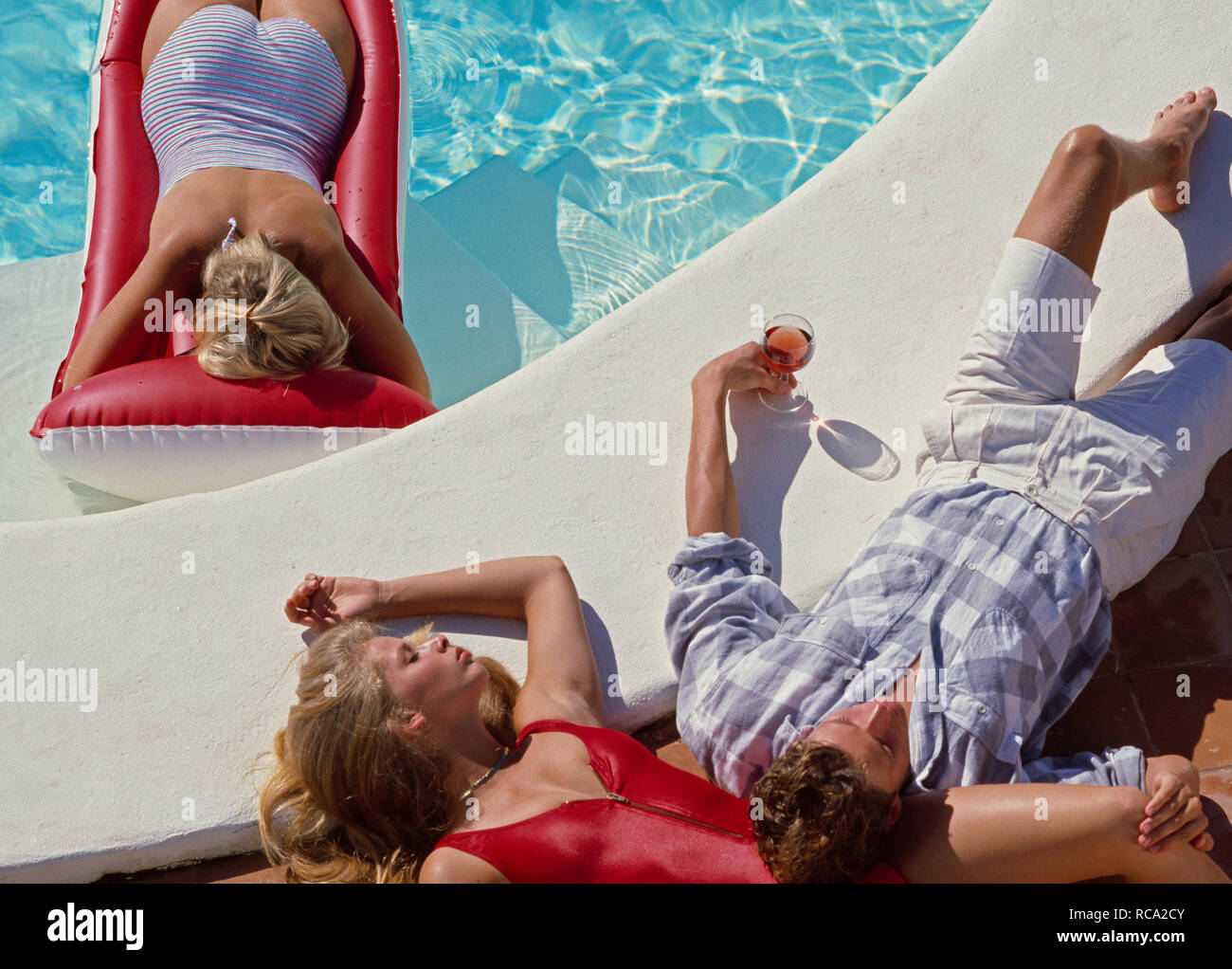 drei junge Leute relaxen am Pool | three young people relaxing at the pool, making holiday *** Local Caption *** Modelrelease vorhanden | model releas - Stock Image