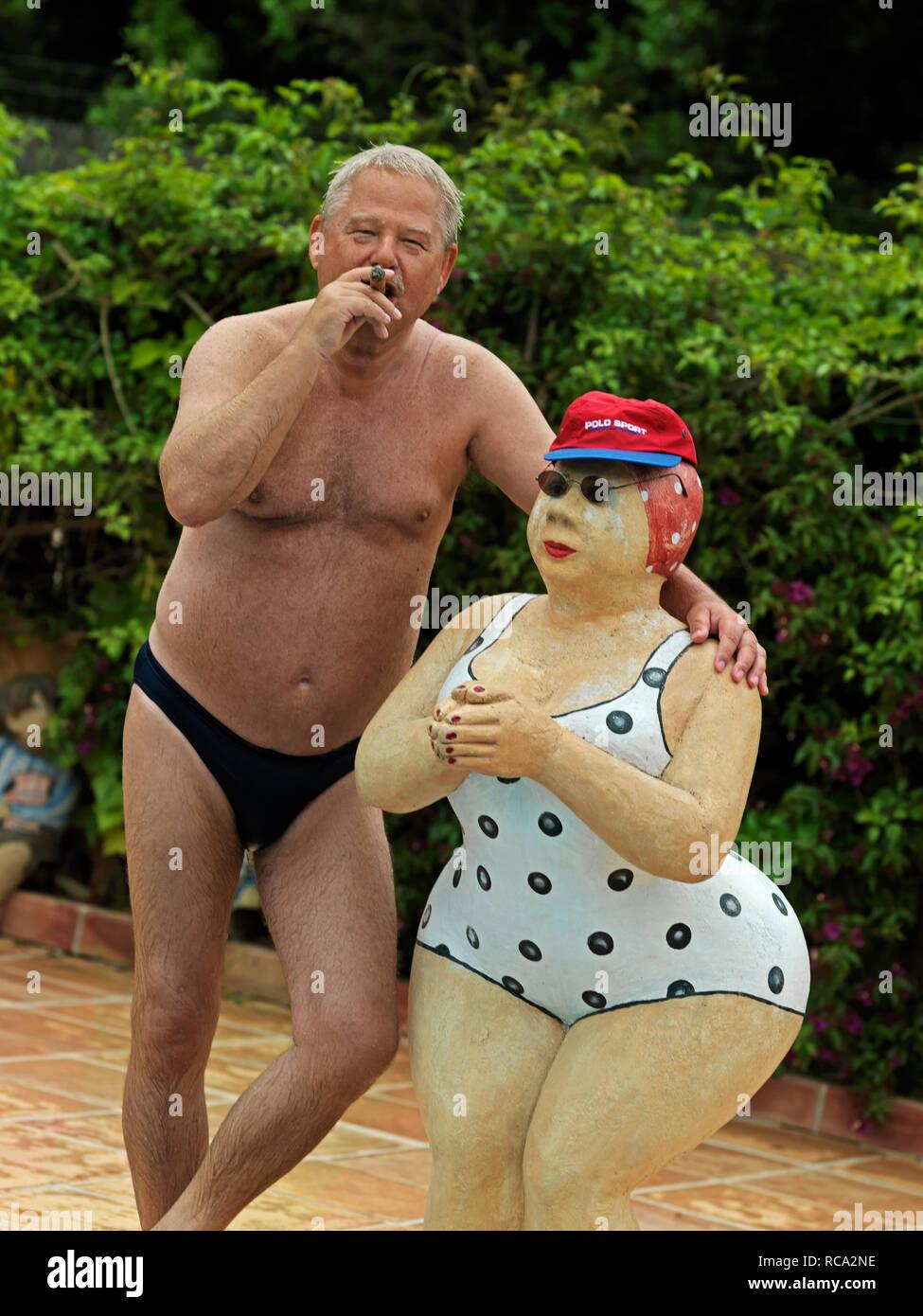 älterer Mann in Badehose steht neben Skulptur von Christel Lechner | elderly man in bathing-trunks standing beside a sculpture from Christel Lechner Stock Photo