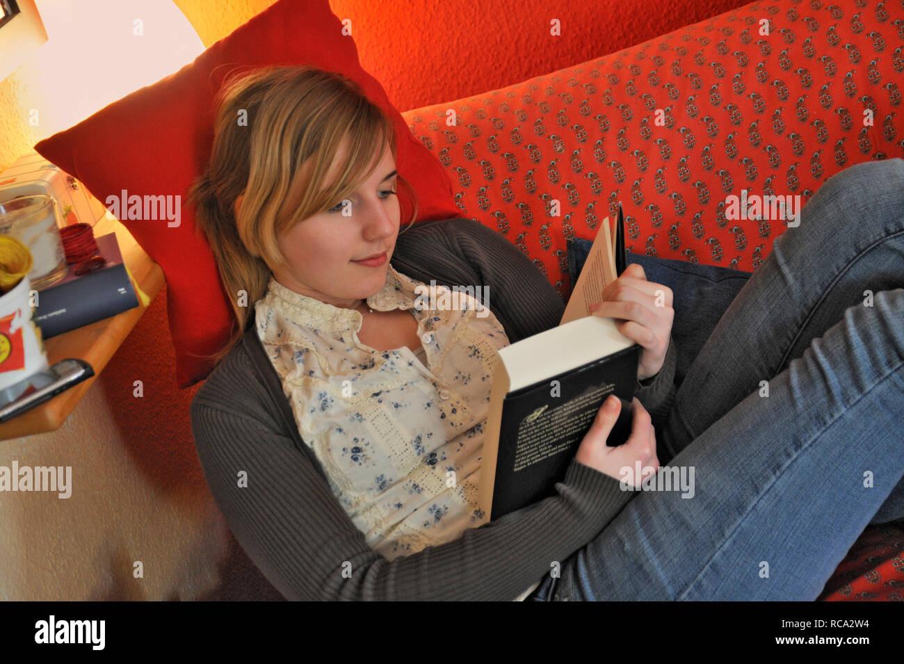 jugendliches Mädchen in ihrem Zimmer liest ein Buch | young female teenager in her room reading a book Stock Photo