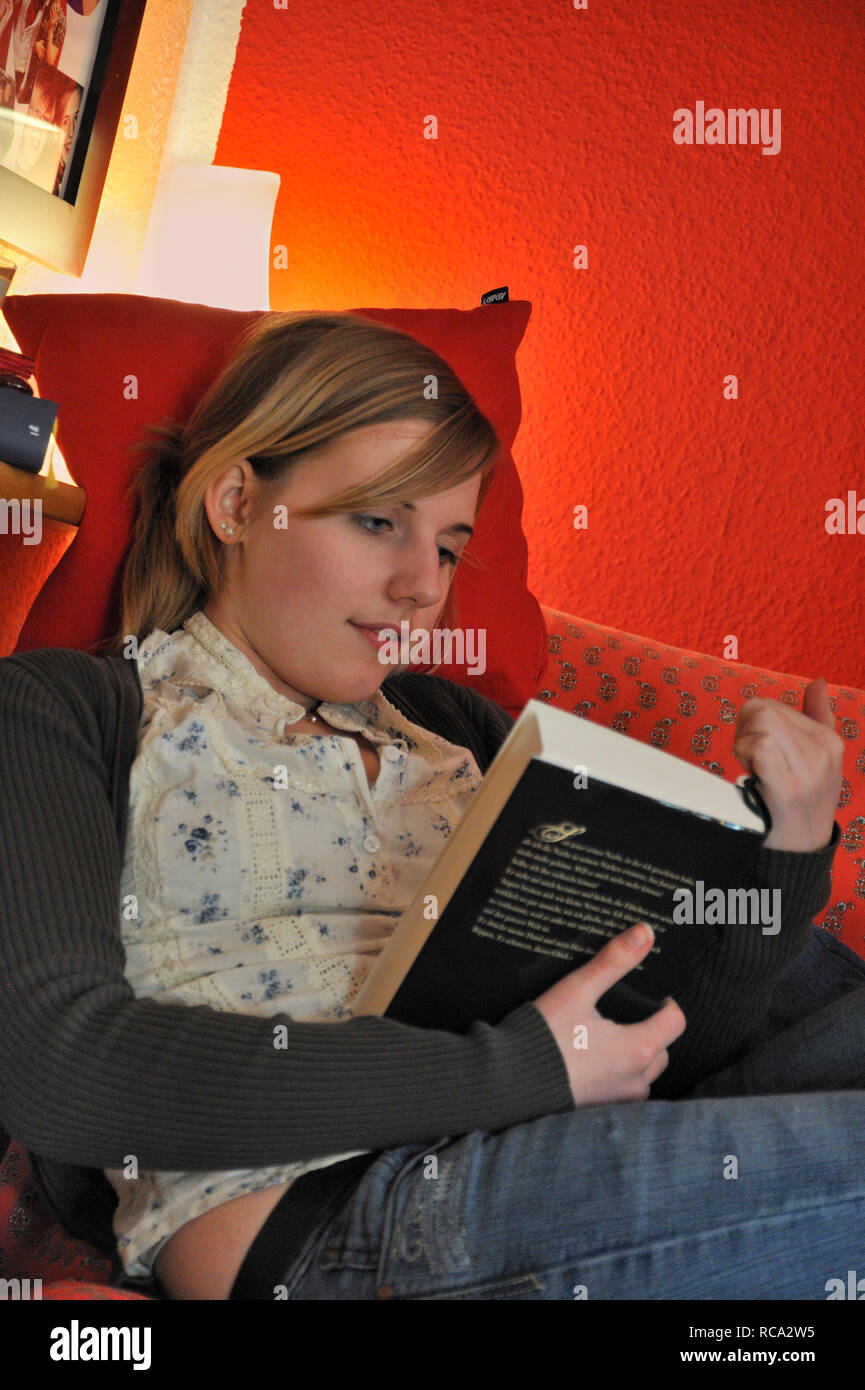 jugendliches Mädchen in ihrem Zimmer liest Buch | young female teenager in her room reading a book - Stock Image