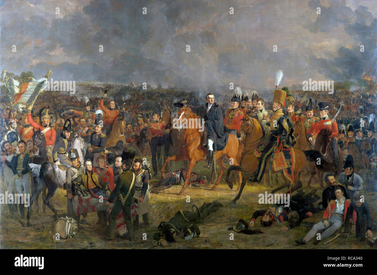 The Battle of Waterloo, after a painting by Jan Willem Pieneman on display in the Rijksmuseum, Amsterdam, Netherlands.  Wellington, centre, receives news that his Prussian allies are close by.  To the left the wounded William, Prince of Orange is carried away on a litter.  The battle rages in the background. - Stock Image