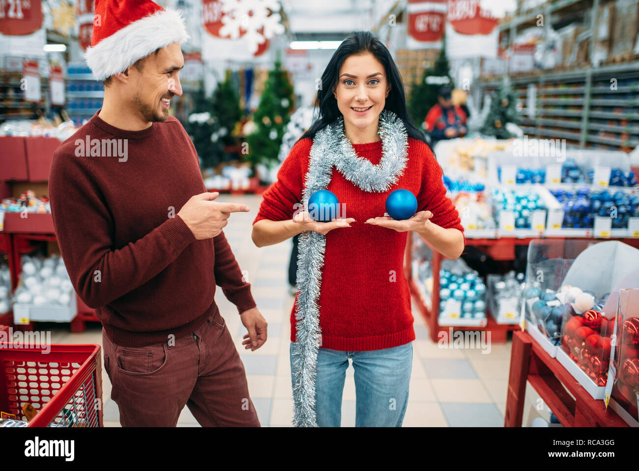Funny couple chooses decorations in shop and jokes, woman puts christmas balls to her chest. December shopping of holiday goods - Stock Image