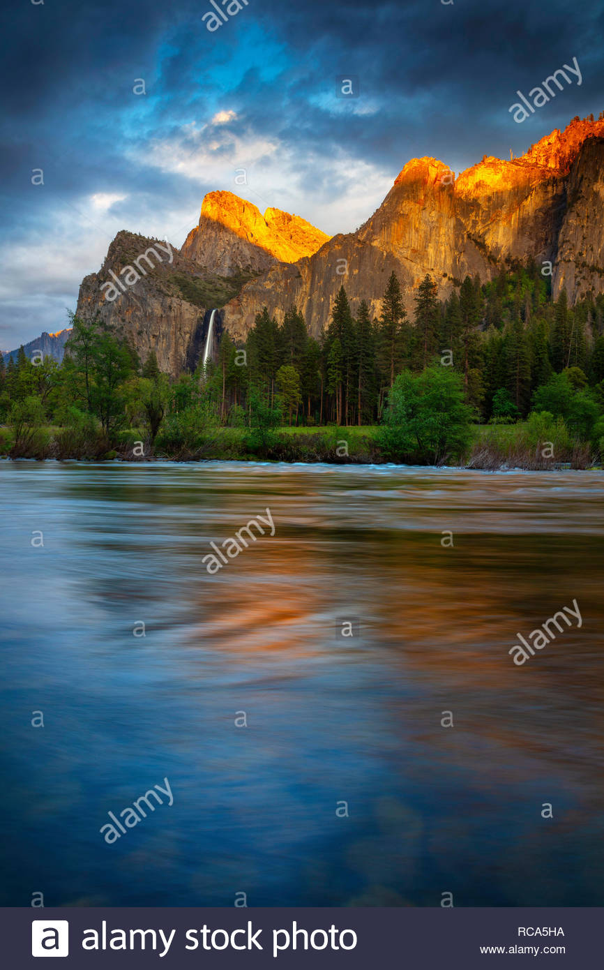 The golden light of sunset reflects off several Yosemite peaks, including the Cathedral Rocks and Leaning Tower, onto the Merced River at Valley View  - Stock Image