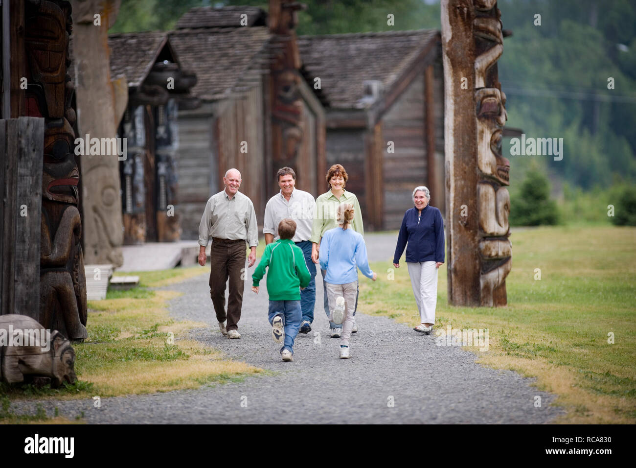 Two children running towards their parents and grandparents. - Stock Image