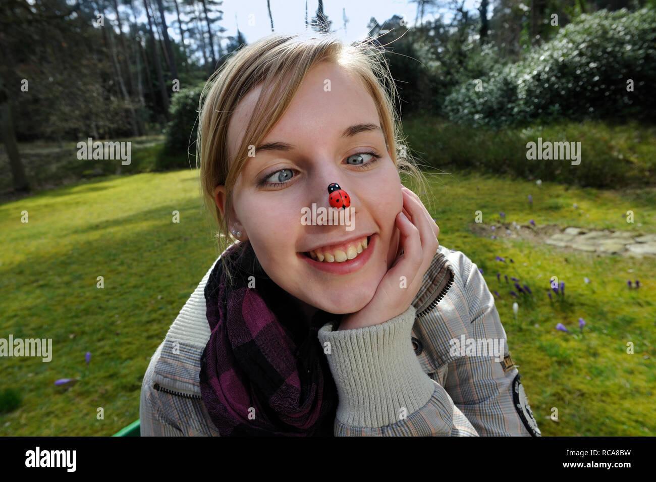 jungendliche Frau mit Marienkäfer auf der Nase | young woman having a beatle on her nose - Stock Image