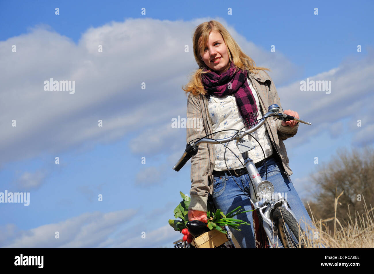 junge Frau mit Fahhrad und Gemüsekorb - junges Gemüse | young women with her bycicle and vegetable basket - Stock Image