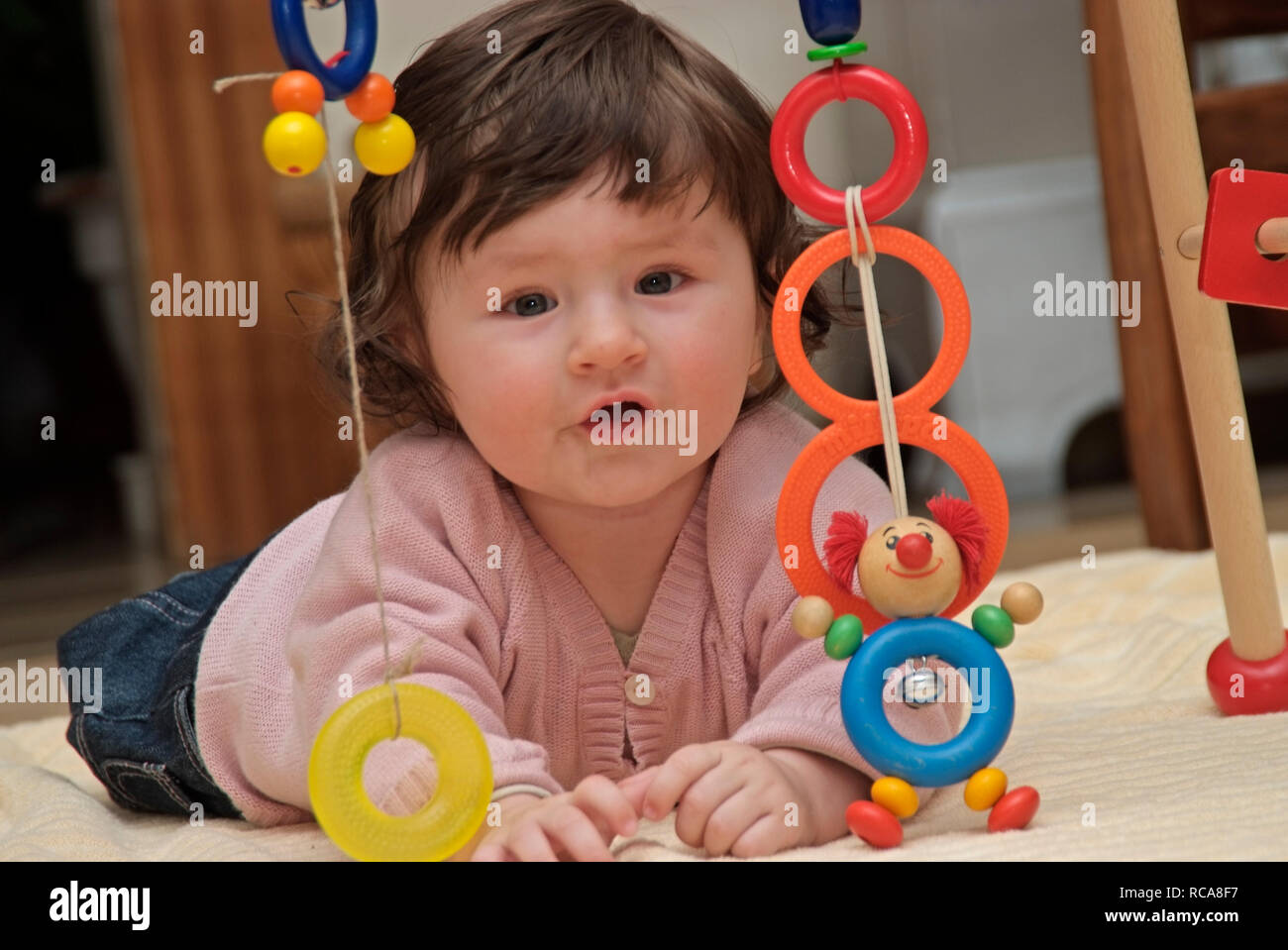 Baby im Zimmer liegt auf dem Boden, Spielzeug | baby lying in a room on the floor, playing with toys Stock Photo