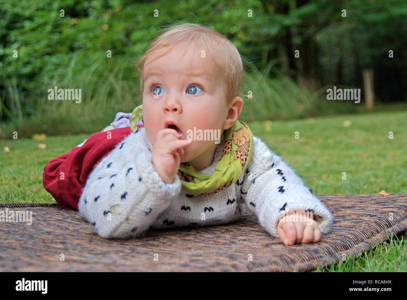 Baby liegt draußen auf einer Matte   baby lying outside on a mattress Stock Photo