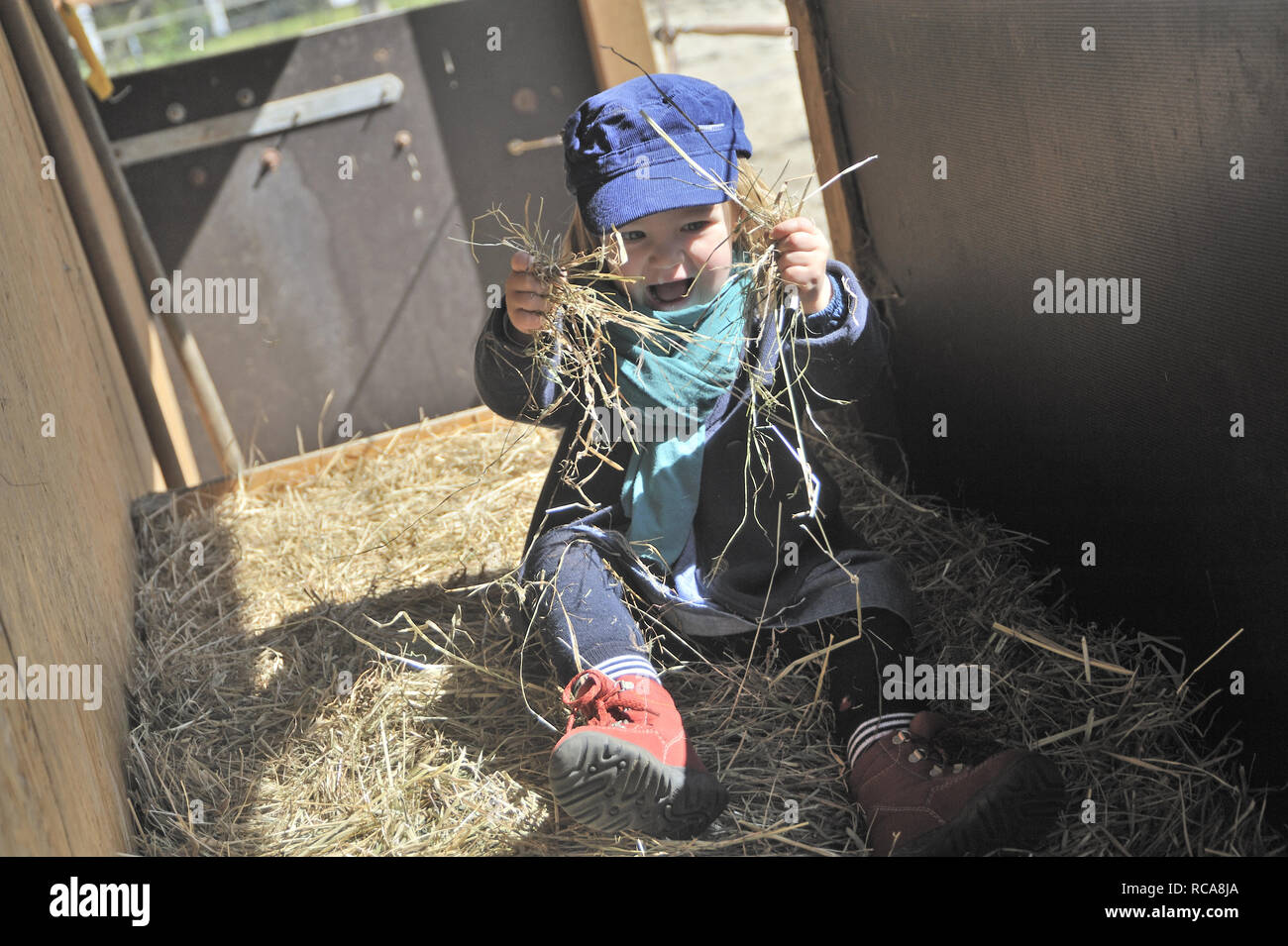 Kind spielt im Stroh | Child plays in straw - Stock Image
