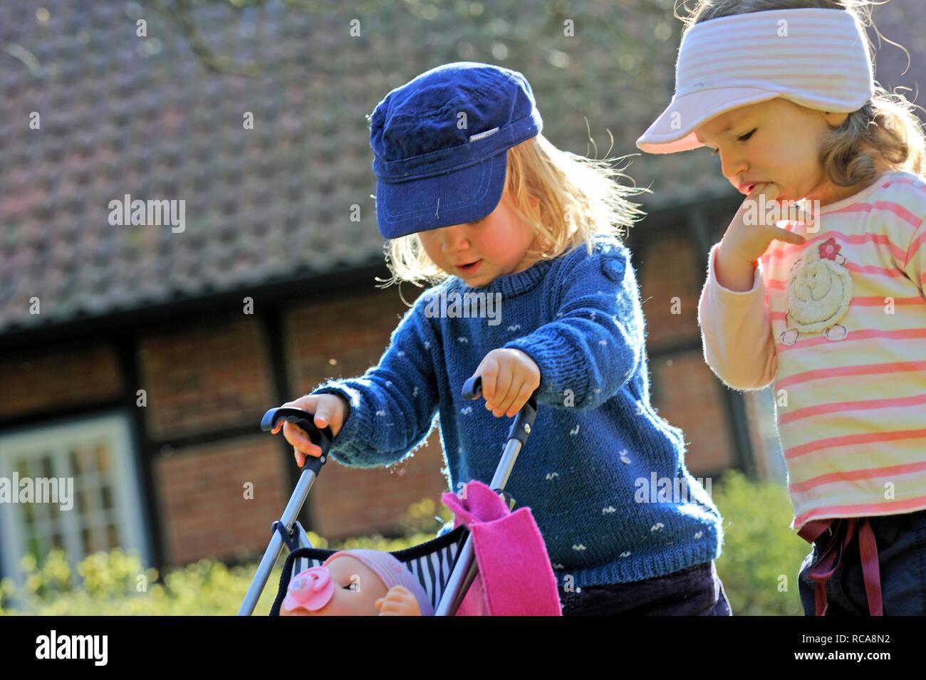 Kinder spielen mit Kinderwagen | Children playing with a buggy Stock Photo