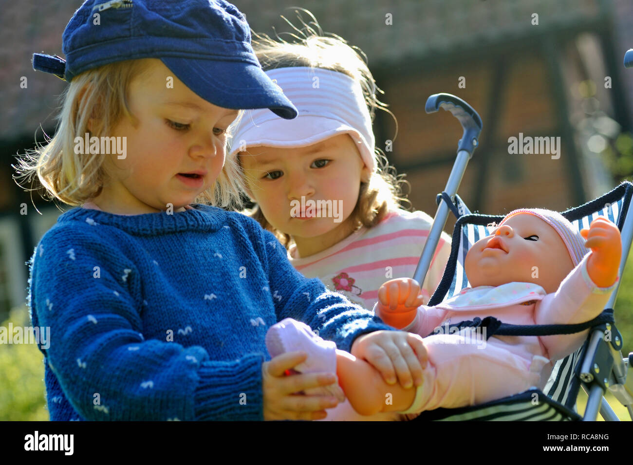 Kinder spielen mit Kinderwagen | Children playing with a buggy Stock Photo