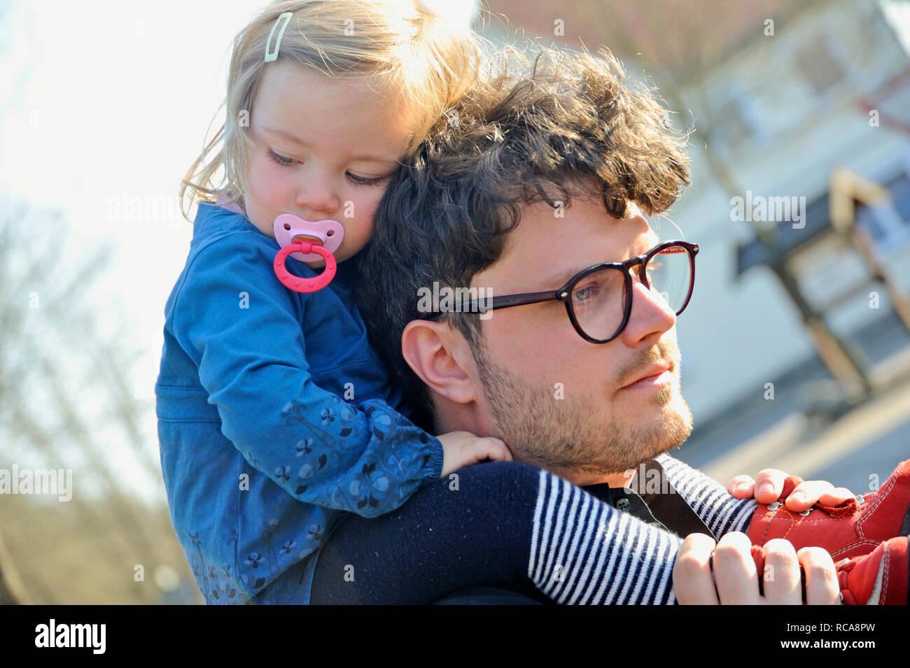 Kleikind, Mädchen, 2 Jahre alt, sitzt beim Vater huckepack auf der Schulter | Child is piggybacked from it's father - Stock Image