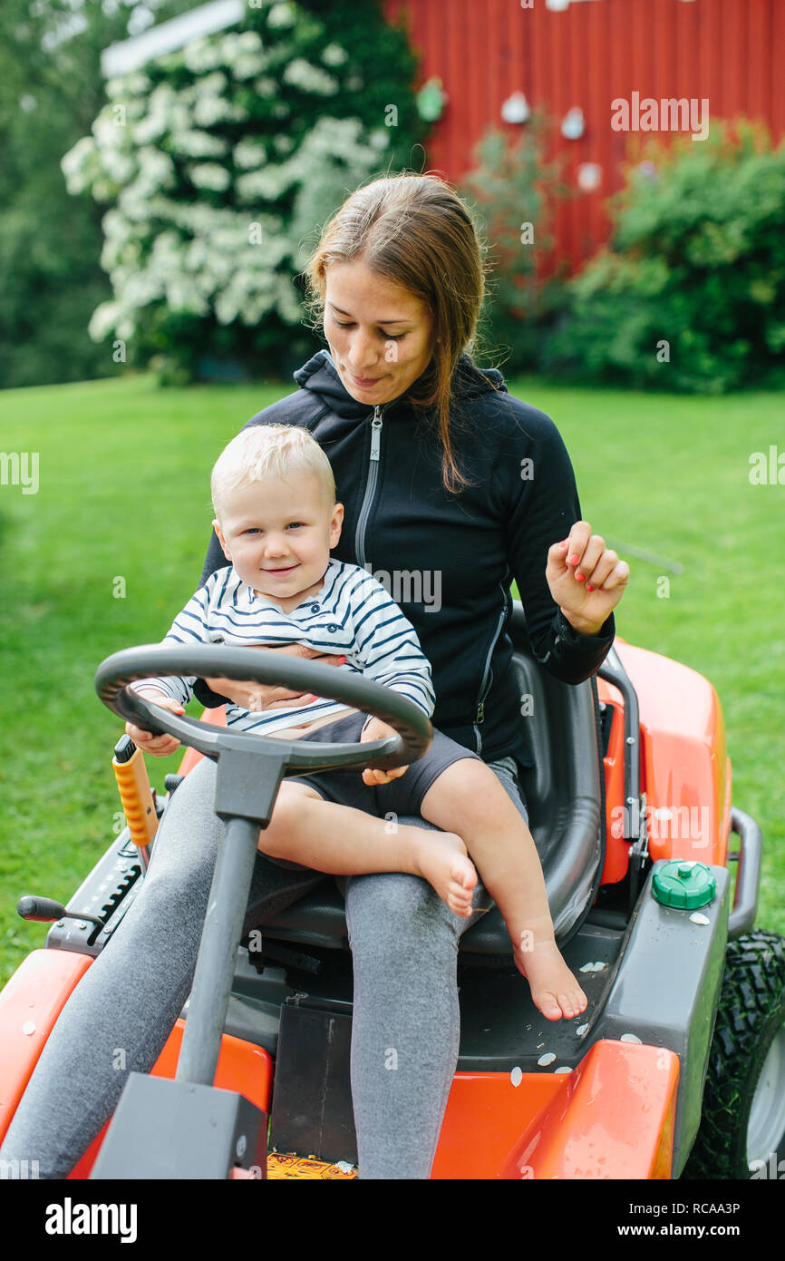 Mother with son on ride-on lawn mower - Stock Image