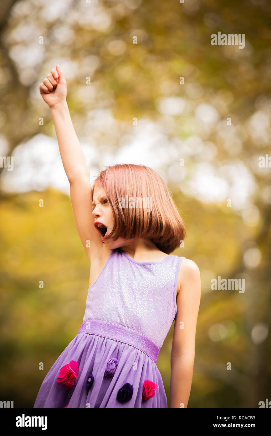 Red headed girl being powerful and fearless outside - Stock Image