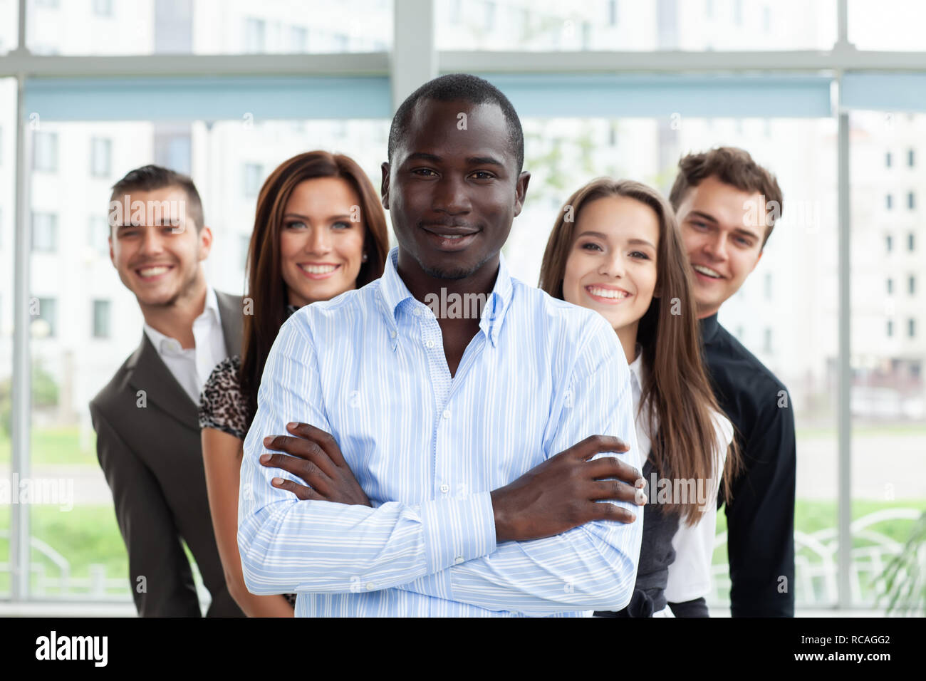 Group of friendly businesspeople with male leader in front. - Stock Image