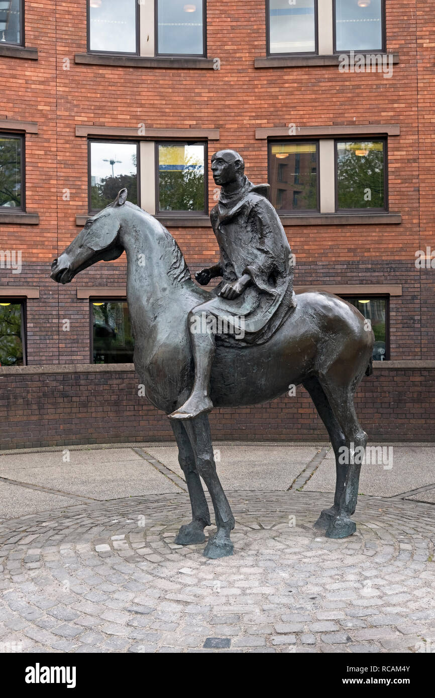 """Cloaked Horseman"", a sculpture by David Backhouse in Bristol, UK representing a medieval traveller arriving at one of the gates in the city wall. - Stock Image"