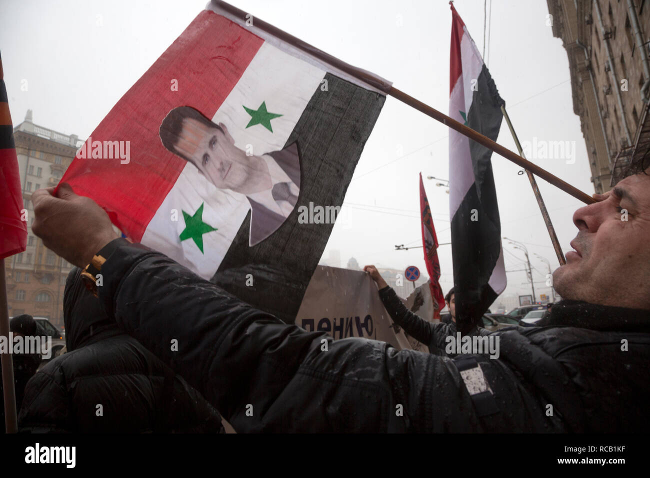 Syrian refugee holding a Syrian flag with a portrait of President Bashar al-Assad, in front of the US Embassy in the center of Moscow, Russia - Stock Image