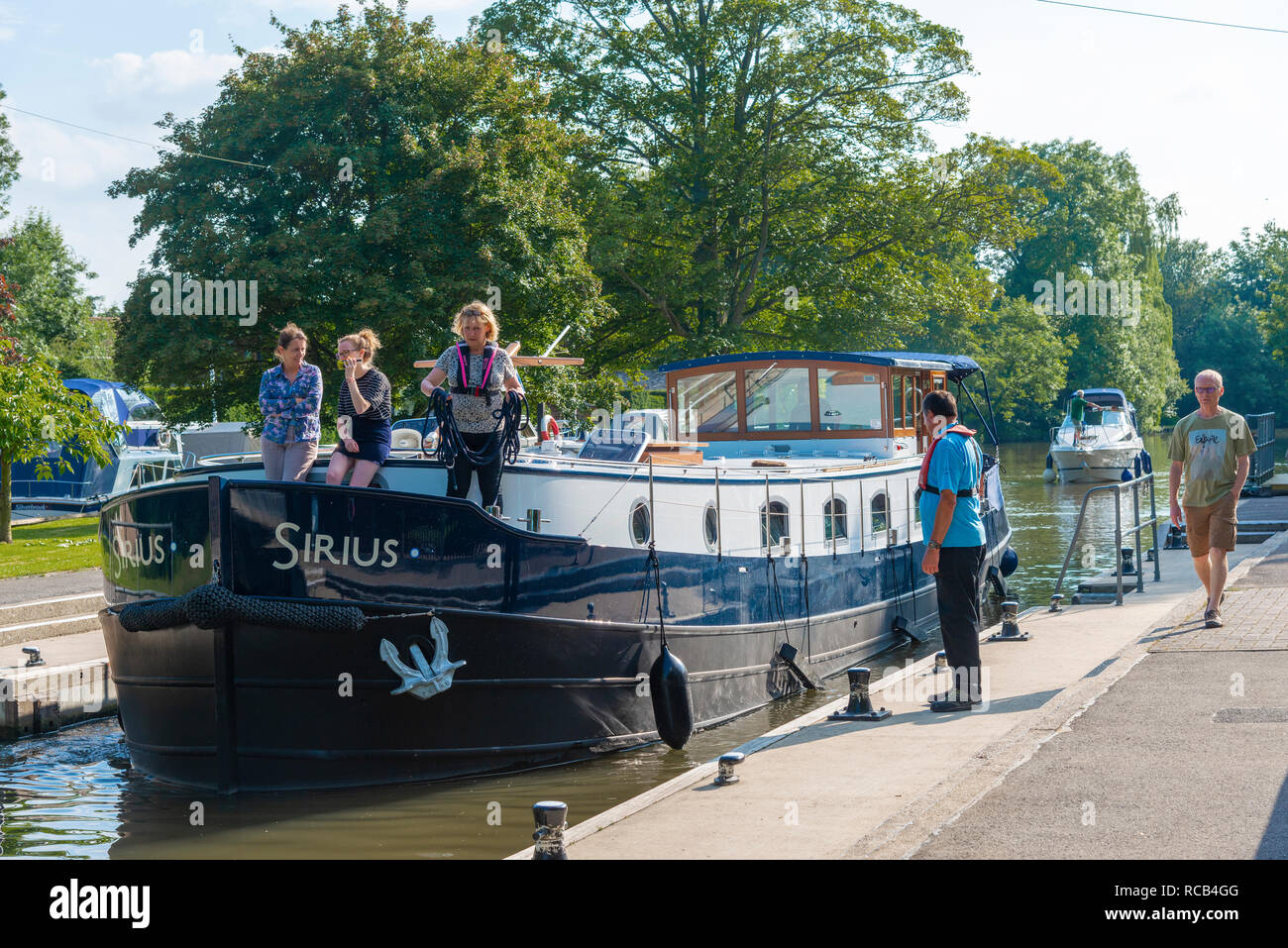 Lock keeper watching barge and cruiser entering Hurley Lock in summer on the River Thames at Hurley near Maidenhead, Berkshire, UK - Stock Image