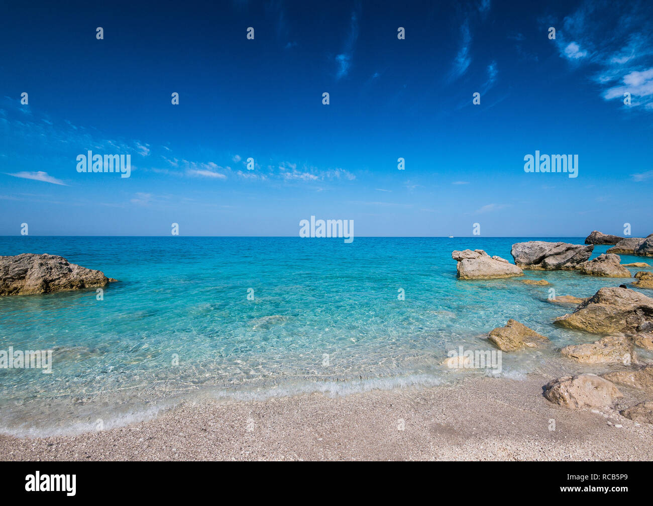 Amazing views of crystal clear milky blue waters of exotic Lefkada beaches with woman gazing the sea horizon - Stock Image