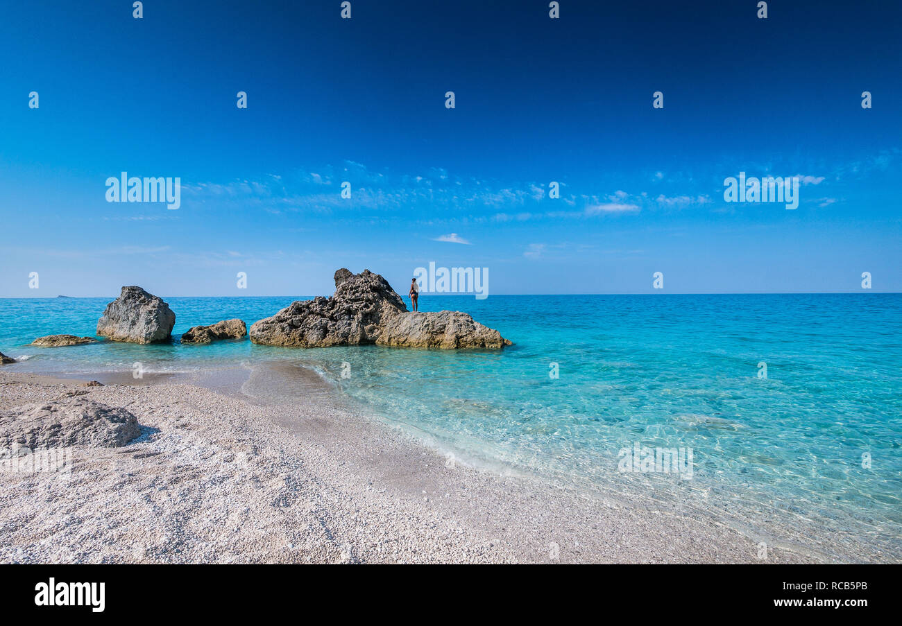 Amazing views of crystal clear milky blue waters of exotic Lefkada beaches with woman gazing the sea horizon Stock Photo